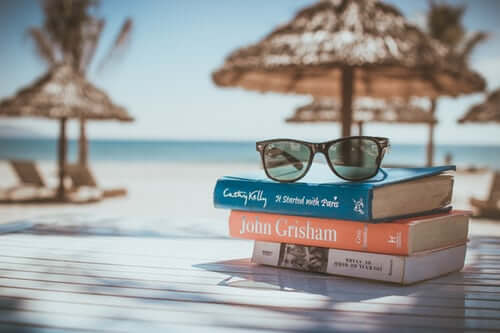 Sunglasses & Books on Beach | The Mustcard